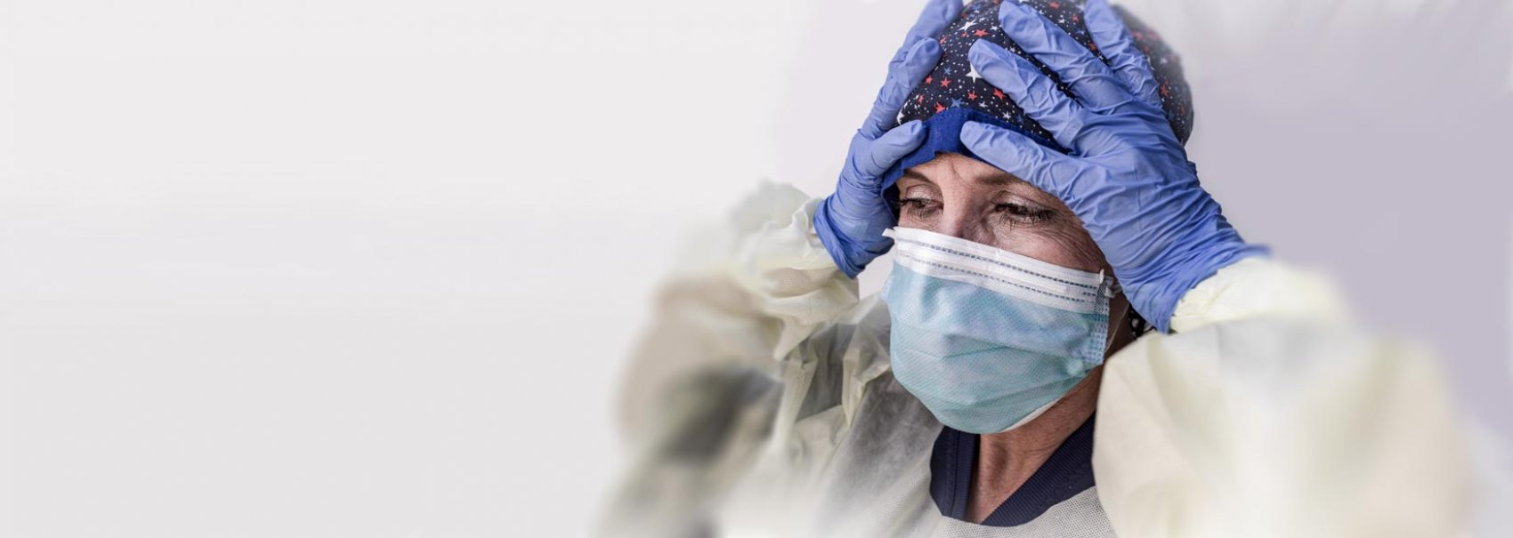 Healthcare worker with mask holding hands on head